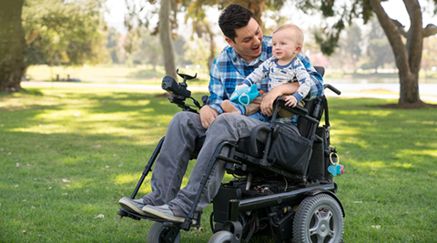 Man in a wheelchair holding a baby